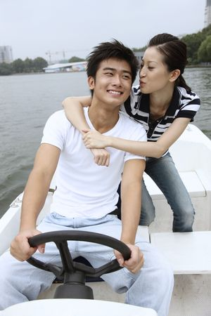 Woman kissing man while traveling on the boat Stock Photo - 10295764