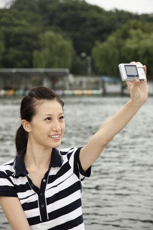 chinese ethnicity: Woman taking picture of herself while traveling on the boat Stock Photo