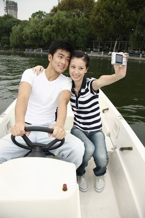 Man and woman taking picture together while traveling on the boat photo