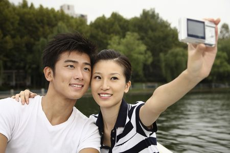 Man and woman taking picture together while traveling on the boat