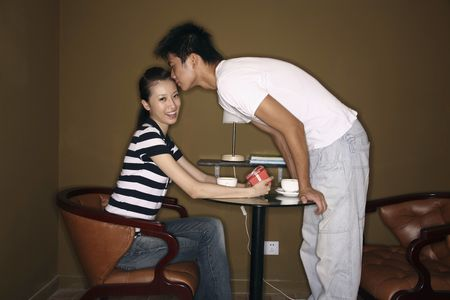 three gift boxes: Woman with a box of gift receiving a kiss from man