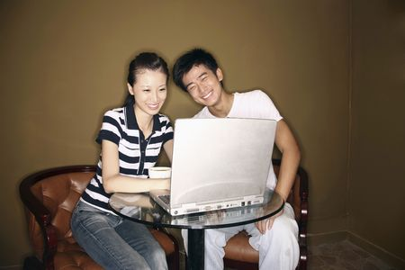 Man and woman using laptop, laughing photo