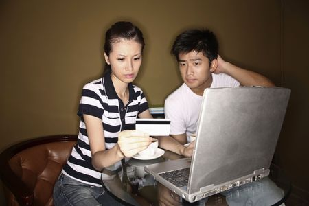 Woman holding credit card while using laptop, man scratching head while looking photo