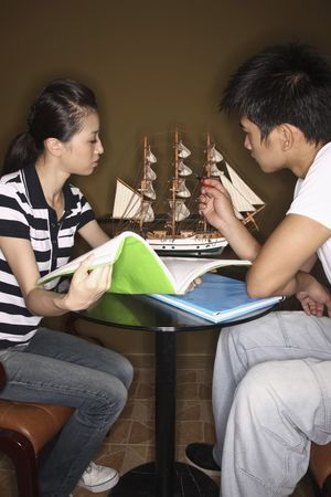 Man pointing at ship model, woman with book watching photo