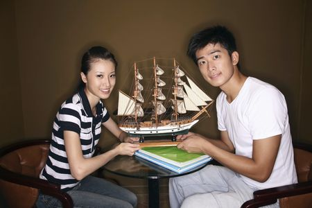 Man and woman holding ship model