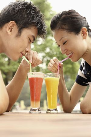 Man and woman enjoying their glasses of fruit juice photo
