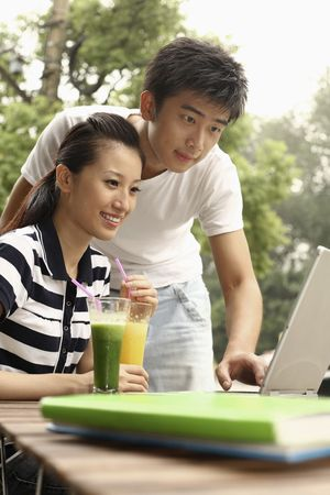 Man using laptop, woman drinking while watching photo