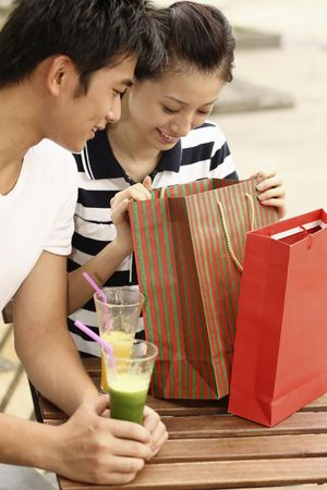 Woman looking into paperbag, man watching photo