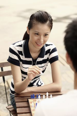 Man and woman playing chess game photo