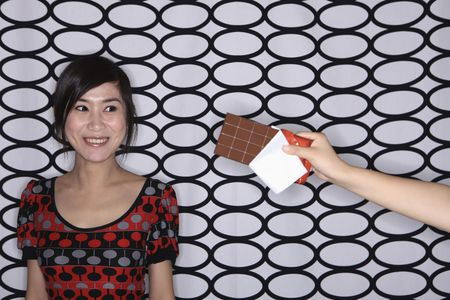 Hand holding out chocolate bar to woman