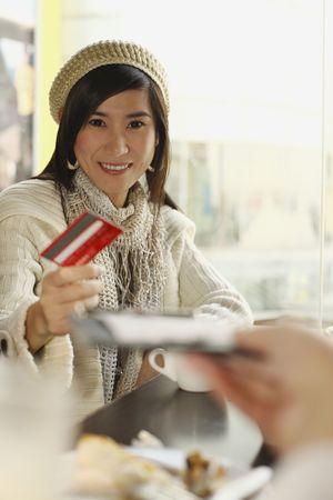 handing: Woman handing waiter credit card Stock Photo