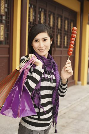 sugarcoated: Woman holding paper bags and sugar-coated strawberries Stock Photo