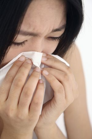 Woman blowing nose with tissue photo