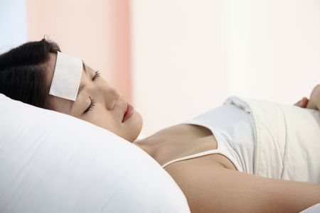 Woman with fever cool gel patch on forehead, resting photo
