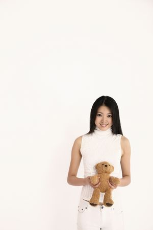 soft toy: Woman holding soft toy smiling at the camera Stock Photo