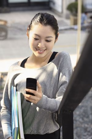 youthful: Woman holding books and text messaging