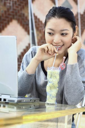 Woman enjoying drink while looking at laptop