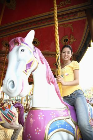 Woman riding on carousel Stock Photo