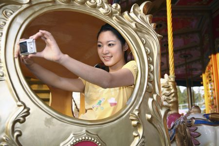 Woman riding in carousel, taking photograph of herself