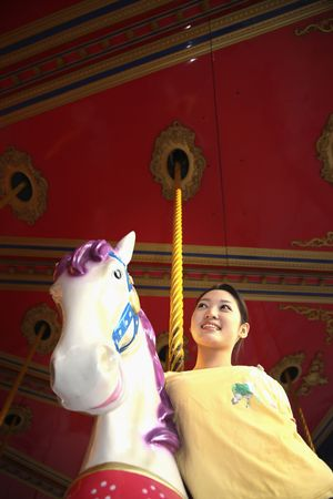 Woman posing beside carousel horse