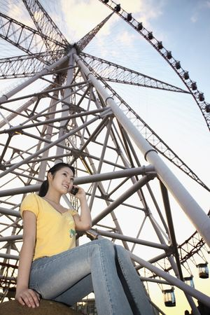 Woman talking on the phone with ferris wheel in the background
