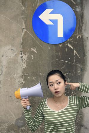 Woman clearing her hearing while holding megaphone Stock Photo