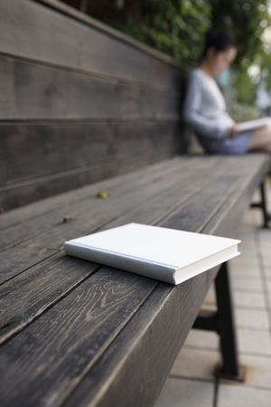 Book on wooden bench, woman reading book in the background