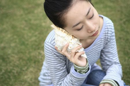 Woman listening to seashell Stock Photo - 10294471