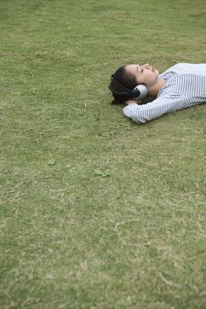 Woman lying on grass listening to headphones Stock Photo - 10295055