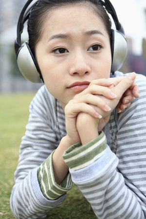 Woman listening to headphones, daydreaming Stock Photo - 10295817
