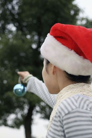 Woman with Christmas hat holding Christmas ornament Stock Photo