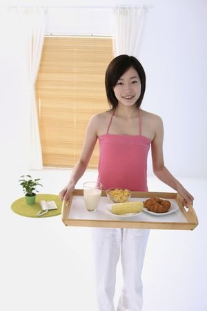 Woman carrying breakfast tray photo