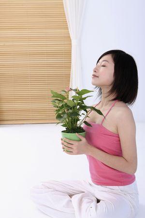 eyes closing: Mujer sosteniendo la planta en maceta, cerrando los ojos