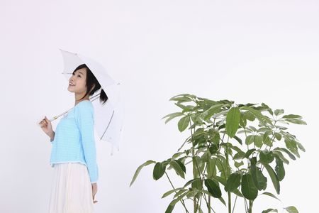 Woman holding umbrella standing beside a plant photo