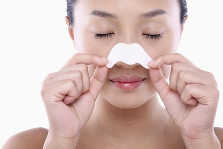 Young woman peeling off pore strips from her nose