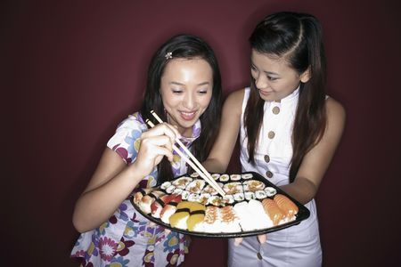 Young woman holding a tray of sushi, another young woman taking sushi with chopsticks photo