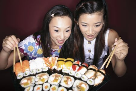 favourite: Young women looking at the variant of sushi Stock Photo