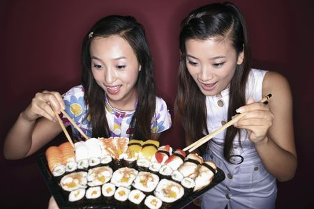 variant: Young women looking at the variant of sushi Stock Photo