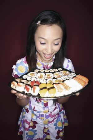 mouth opened: Young woman looking at the variant of sushi with her mouth opened Stock Photo