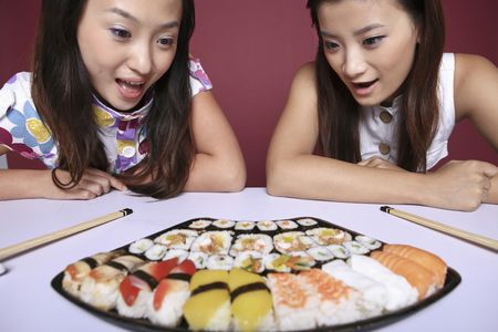Young women looking at the variant of sushi with their mouths opened photo