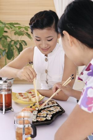 Young women enjoying japanese cuisine photo