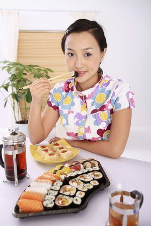 Young woman enjoying japanese cuisine photo