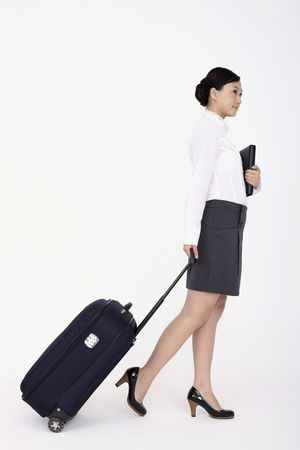 Young woman holding organizer and pulling suitcase