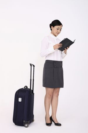 Young woman reading organizer, suitcase beside her Stock Photo - 4778851