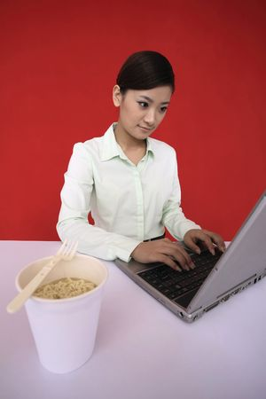 Young woman using laptop, a cup of instant noodle by the side photo