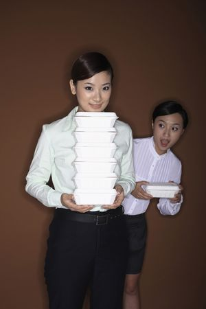 Young woman with a stack of take out food, another woman looking shockingly at her photo