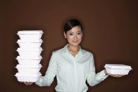 Young woman holding a stack of take out food on one hand and another take out container on the other hand