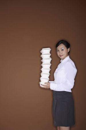 Young woman with a stack of take out food photo