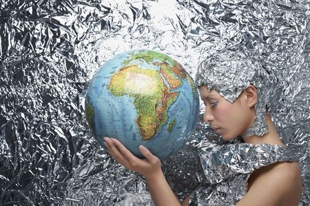 Woman wearing foil accessories among foil background holding globe photo