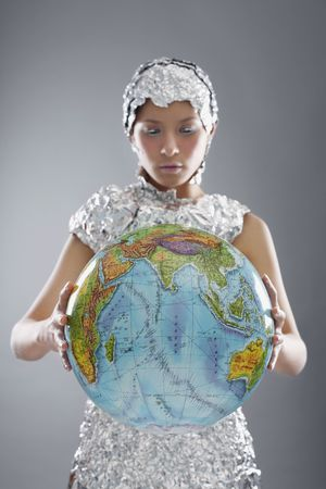 Woman wearing foil accessories holding globe photo